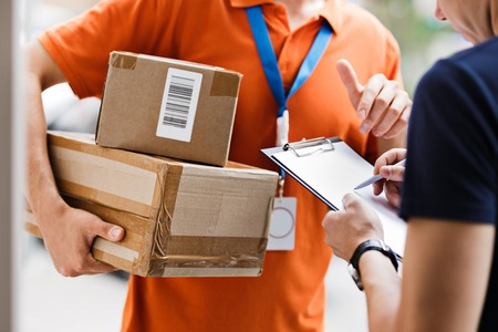 A person wearing an orange T-shirt and a name tag is delivering a parcel to a client, who is putting his signature on the receipt. Friendly worker, high quality delivery service. Banque d'images