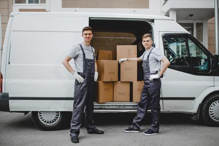 Deux jeunes beaux travailleurs souriants portant des uniformes sont debout