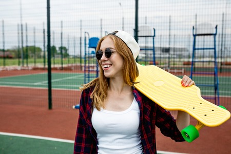A pretty smiling blond girl wearing checkered shirt, white cap and sunglasses is standing in front of the guardlattice on the sports field with a yellow longboard on her shoulder. Sport and cool style. Stock Photo
