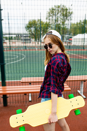 A pretty blond girl wearing checkered shirt, white cap and sunglasses is standing on the sports field with a yellow longboard in her hand. Sport and cool style.