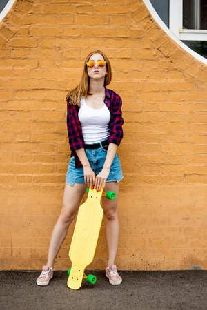 A girl wearing sunglasses, checkered shirt and denim shorts is standing in front of the brick wall and holding a yellow longboard in front of her. Cool style.