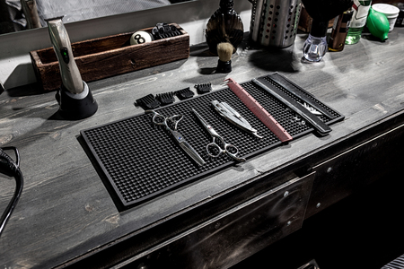 The tools of the barber lie on a black mat on the desktop