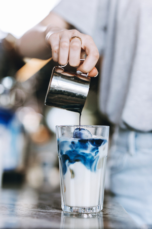 A youthful pretty slim blonde,wearing casual outfit, pours coffee into a glass of milk in a cozy coffee shop. Reklamní fotografie