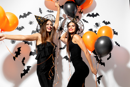 Two beautiful brunette women in witches hats are with black and orange balloons on a white background with bats and spiders.