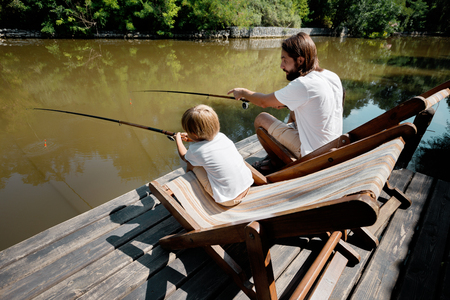 Young dark-haired father and his little son are sitting in recliners on the wooden pier with fishing rods and fishing.