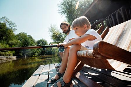 Kleiner blonder Junge und sein hübscher Vater sitzen in Liegen auf dem hölzernen Pier und fischen. Standard-Bild