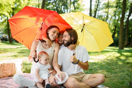 Happy parents with two kids have a rest on the lawn under the bright red and yellow umbrellas covering them from the sun.