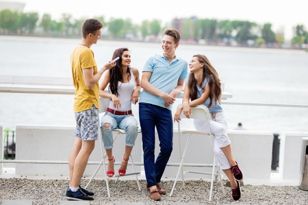 Una compañía de amigos guapos se ríe y socializa en el agradable café de verano. El río está al fondo. Entretenimiento, pasando un buen rato. Amistad.