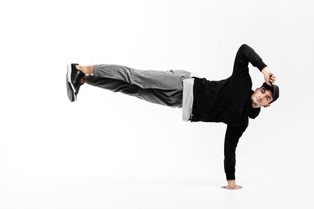 Stylish young man is dancing breakdance. He is standing on one arm and lifting both legs up.