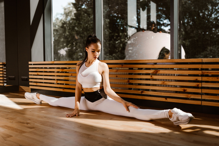 Young slender dark-haired girl dressed in white sports top and tights is doing the splits in the gym