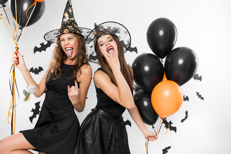 Two brunette girls in black dresses and witch`s hats have fun with balloons on the background of the wall with bats. Halloween