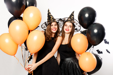 Two beautiful women in black dresses and witch`s hats have fun with black and orange balloons. Halloween party Stok Fotoğraf
