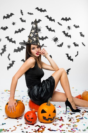 Girl wearing black dress, witch`s hat and high heels sits on the pumpkin. Halloween pumpkins are next to her