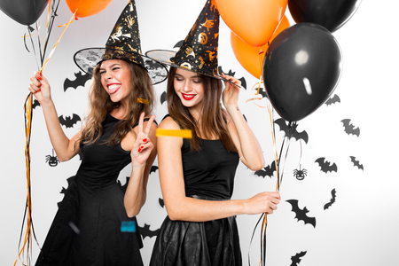 Two brunette girls in black dresses and witch`s hats have fun with balloons and confetti. Halloween party