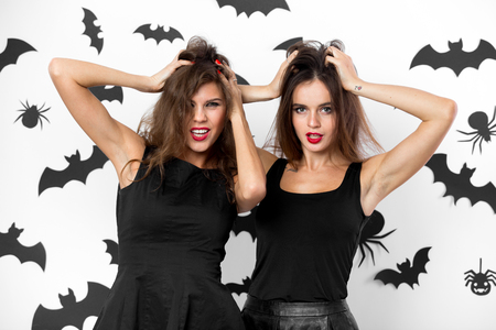 Two brunette girls dressed in black dresses grimace on the background of the wall with bats. Halloween party.