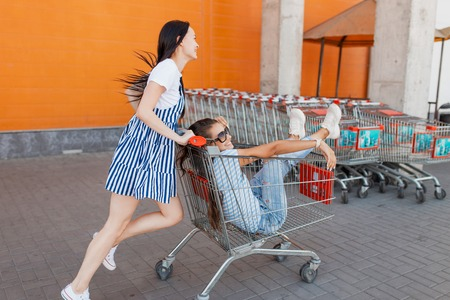 Two pretty slim dark-haired ladies,wearing casual outfit,have fun with a grocery cart near the shopping center. Foto de archivo