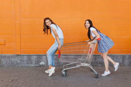 Two pretty slim dark-haired ladies,wearing casual outfit,stand with a grocery cart near the shopping center.