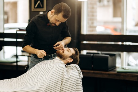 Fashion barber with mustache dressed in a black shirt with a red bow tie trims mens beard in the barbershop