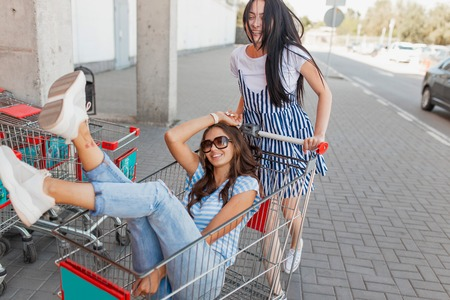 Two pretty slim dark-haired ladies,wearing casual outfit,have fun with a grocery cart near the shopping center. 版權商用圖片