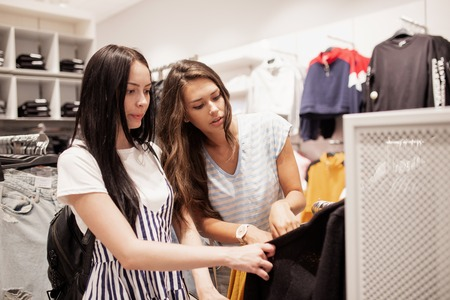 Two young smiling slim girls with long dark hair,wearing casual style,have shopping in a modern mall.