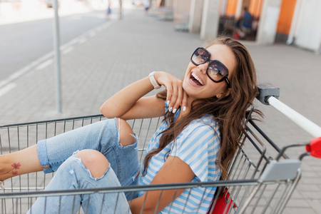 A young pretty dark-haired girl with glasses,wearing casual style,is sitting in a grocery cart near the shop.