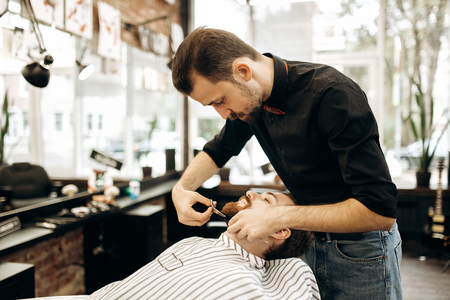 Fashion barber with mustache dressed in a black shirt with a red bow tie tidies up mens beard  and scissors it in the barbershop 免版税图像