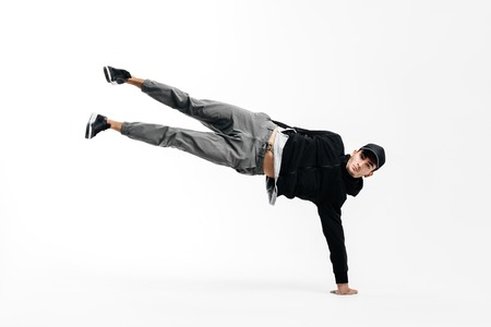 Stylish young dancer is dancing breakdance. He is standing on one arm and lifting both legs up.