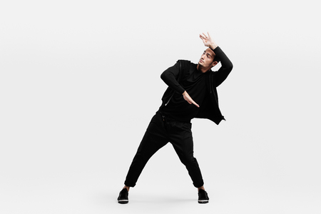 Dark-haired stylish man dressed in a stylish black clothes is dancing street dance. He makes stylized movements with his hands 免版税图像
