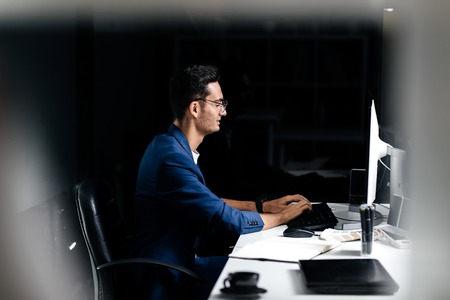 The architect in glasses dressed in a blue jacket sits at the desk and works on the computer in the office