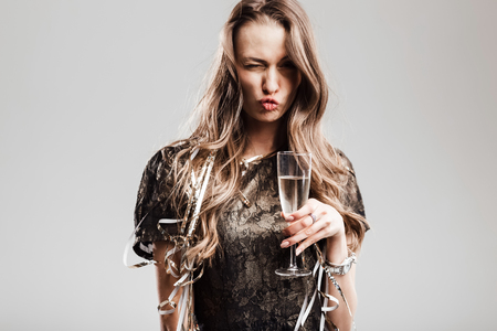 Beautiful girl dressed in stylish elegant black dress holds glass of champagne grimacing on a white background Stock Photo