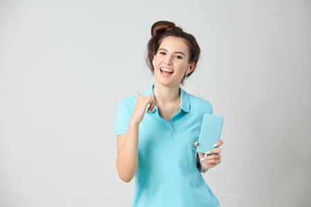Joyful girl dressed in light blue t-shirt smiles and keeps mobile phone in her hand