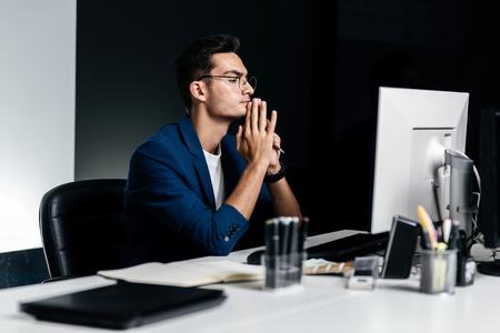 The architect in glasses dressed in a blue jacket sits at the desk in front of the computer and thinking