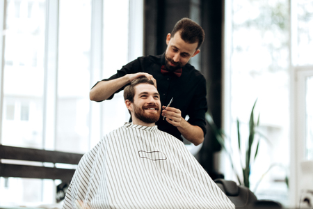 Stylish mustachioed barber dressed in a black shirt with a red bow tie scissors the hair of a young man in a barbershop