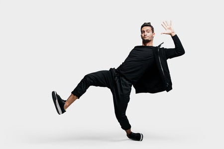 Handsome young  man dressed in a black clothes is dancing street dance. He makes stylized movements with his hands