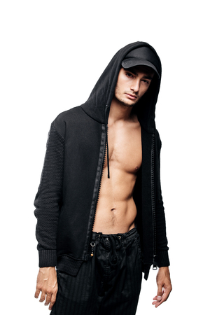 Handsome  young dancer dressed in black pants, a sweatshirt on a naked torso and a hood on the cap stands on a white background