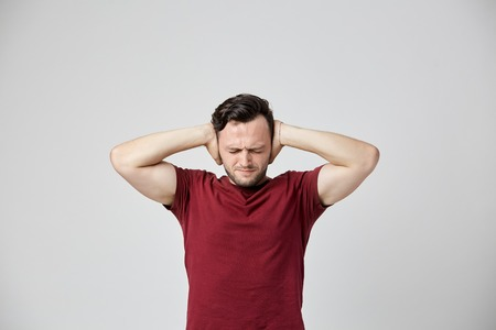 Annoyed man in the burgundy t-shirt closed ears with his hands