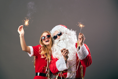 Santa Claus and young beautiful mrs. Claus in sunglasses are holding sparklers in their hands on the gray background.  Christmas