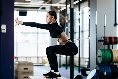 Slim dark-haired girl dressed in black sports clothes is doing squats on the box next to the sport equipment in the gym