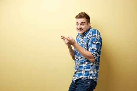 Surprised guy dressed in a plaid shirt and jeans stands next to yellow wall in the studio and points with his hands somewhere