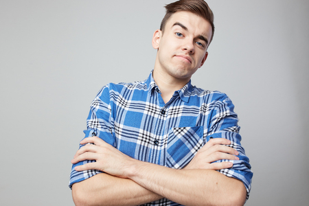 Self Confident man dressed in a plaid shirt is on a grey wall in the studio Stock Photo