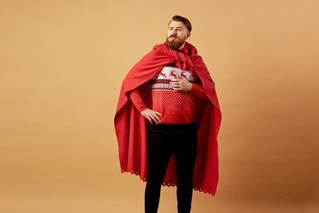 Red-haired man with beard dressed in a red and white sweater with deer and red cape   and sleepers stands on a beige background Stock Photo