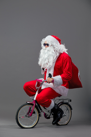 Funny Santa Claus in sunglasses and headphones with the bag with Christmas gifts on his back rides a bicycle on the white. Stock Photo