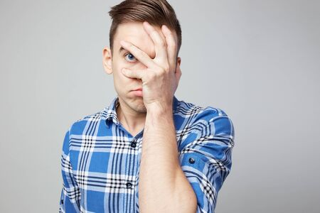 Scared guy dressed in a plaid shirt and jeans closes his face with his hand on a white background in the studio 版權商用圖片