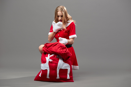 Young and beautiful mrs.Santa Claus dressed in the red robe and white gloves sits near the bag  with Christmas gifts and looks surprised in it on the gray wall.