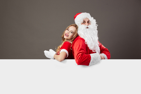 Santa Claus and young mrs. Claus stand back to back  behind a white canvas and leans on it on the gray wall.
