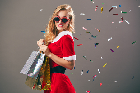 Young and beautiful woman in sunglasses dressed in the red dress and white gloves holds the bags with gifts and smiles on the gray wall with confetti.