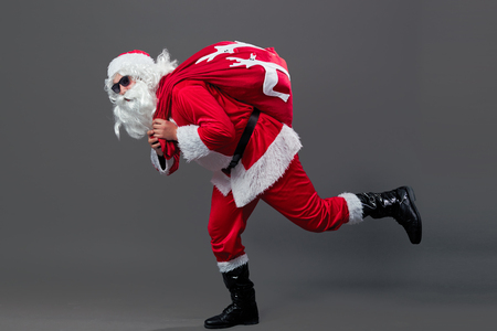Santa Claus with sunglasses runs with the bag in Christmas gifts on his back on the white wall. Stockfoto