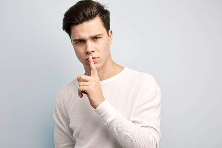 Dark-haired guy dressed in a white long sleeve t-shirt keeps his finger on his lips on a white background Reklamní fotografie