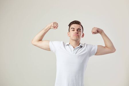 Guy dressed in a white t-shirt and jeans is full of strength and energy on a white background in the studio