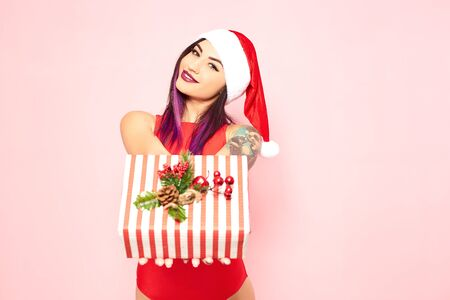 Bright girl with purple hair tips and tattoo on her arm dressed in red swimsuit, Santas hat and white fur bracelets holds a christmas gift in her hands on the background of pink wall Reklamní fotografie